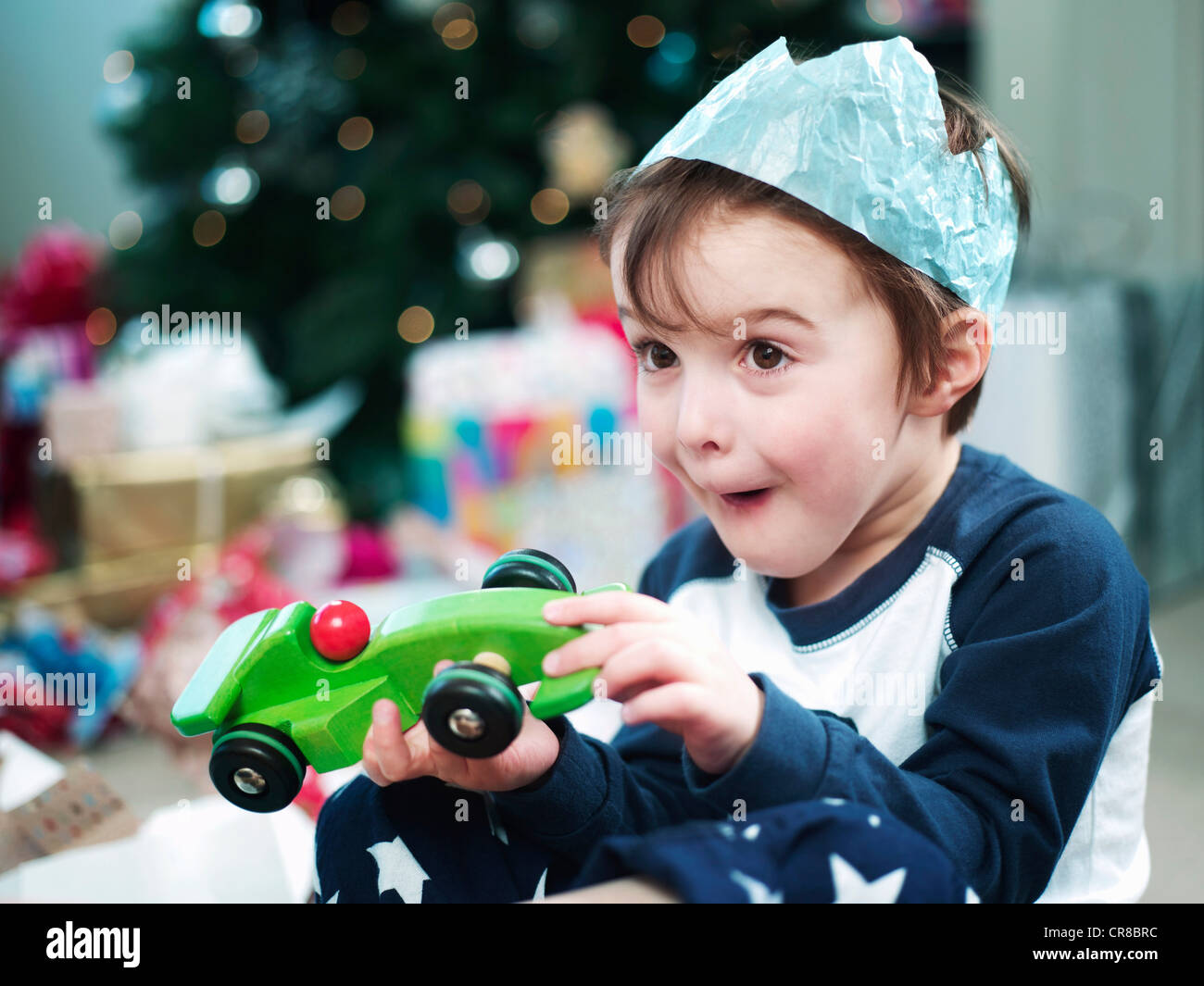 Boy opening christmas presents - Stock Image
