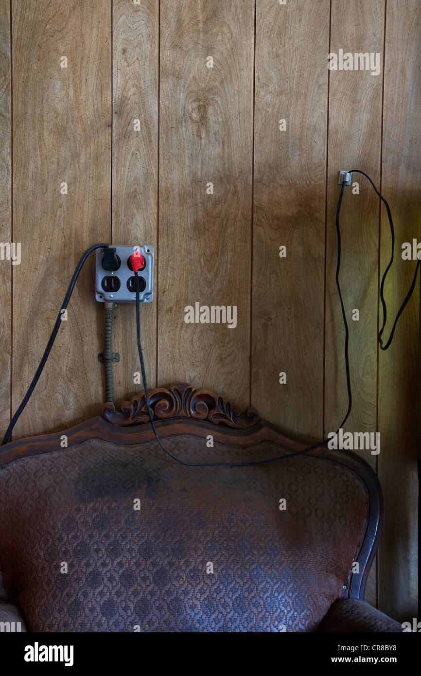 Electrical outlet and wires above old chair - Stock Image