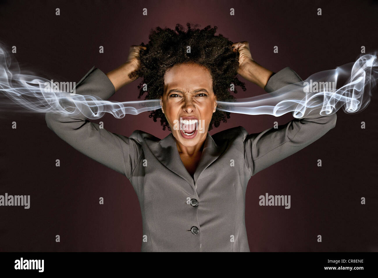 Frustrated woman with smoke coming from ears - Stock Image