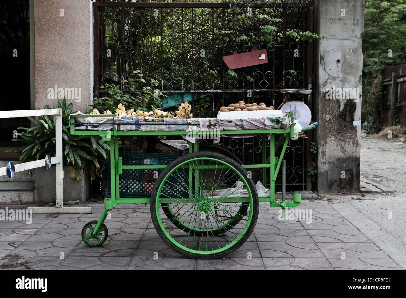 Green cart parked in market, Bangkok, Thailand - Stock Image