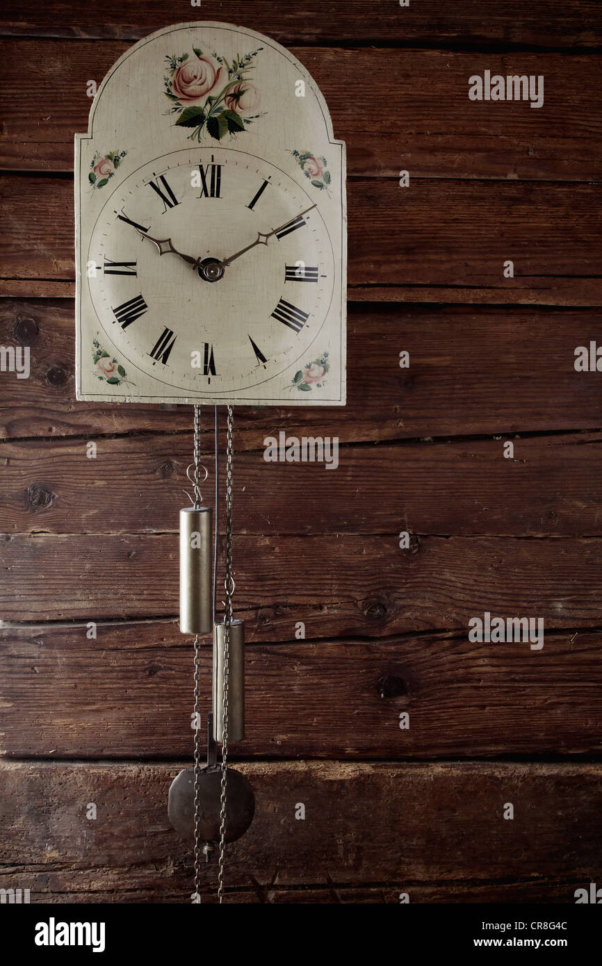 Antique Black Forest wall clock with an apple-rose motif hanging on a rustic wooden wall - Stock Image