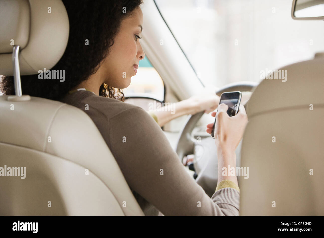 Young woman text messaging on cellphone from car - Stock Image