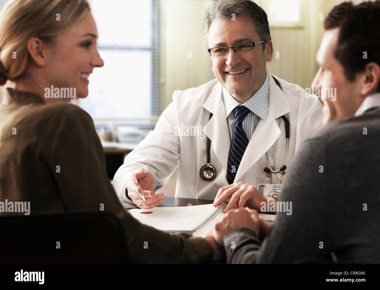 Young couple in doctor's office receiving good news - Stock Image