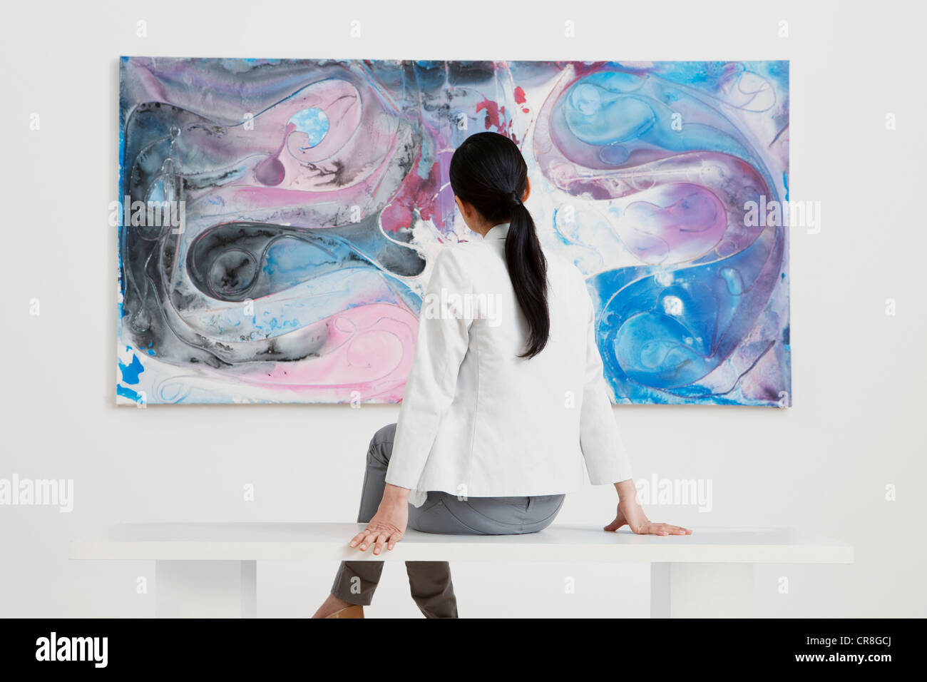Young woman looking at oil painting in gallery - Stock Image