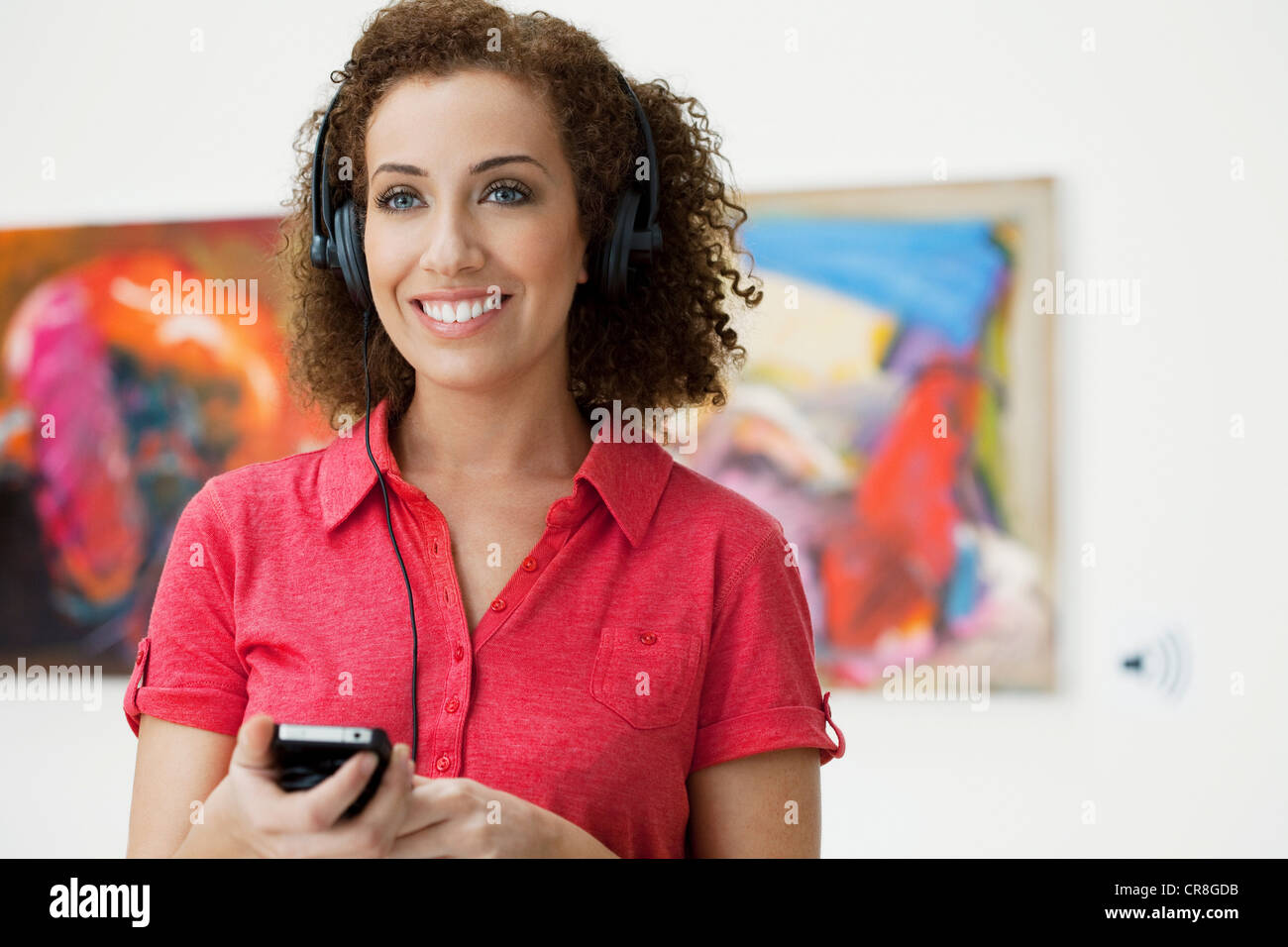 Young woman using audio guide in art gallery - Stock Image