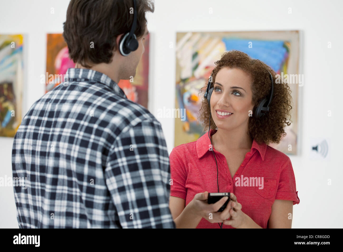 Young couple using audio guides in art gallery - Stock Image