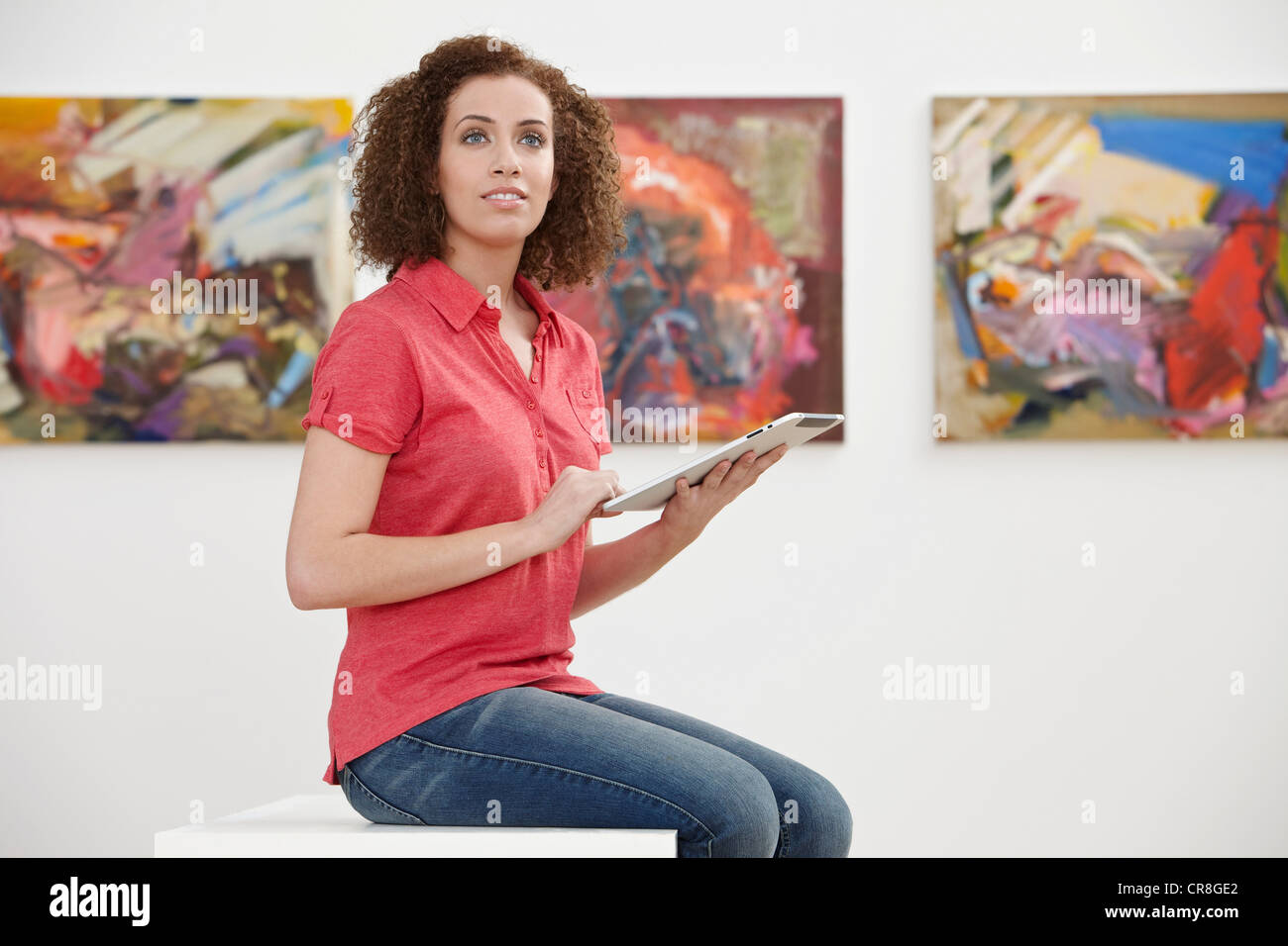Young woman using digital tablet in art gallery - Stock Image