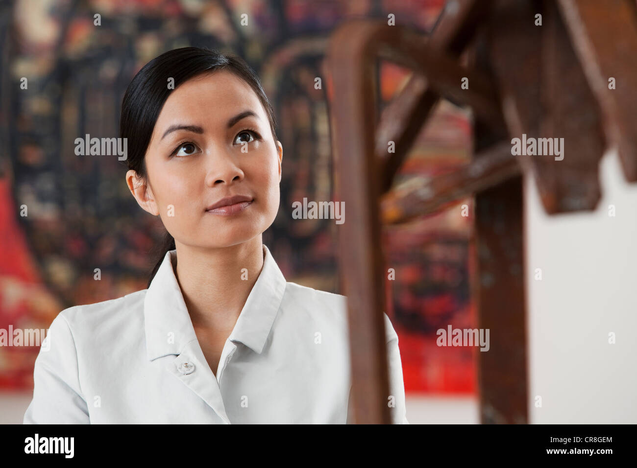 Young woman looking at sculpture in art gallery - Stock Image