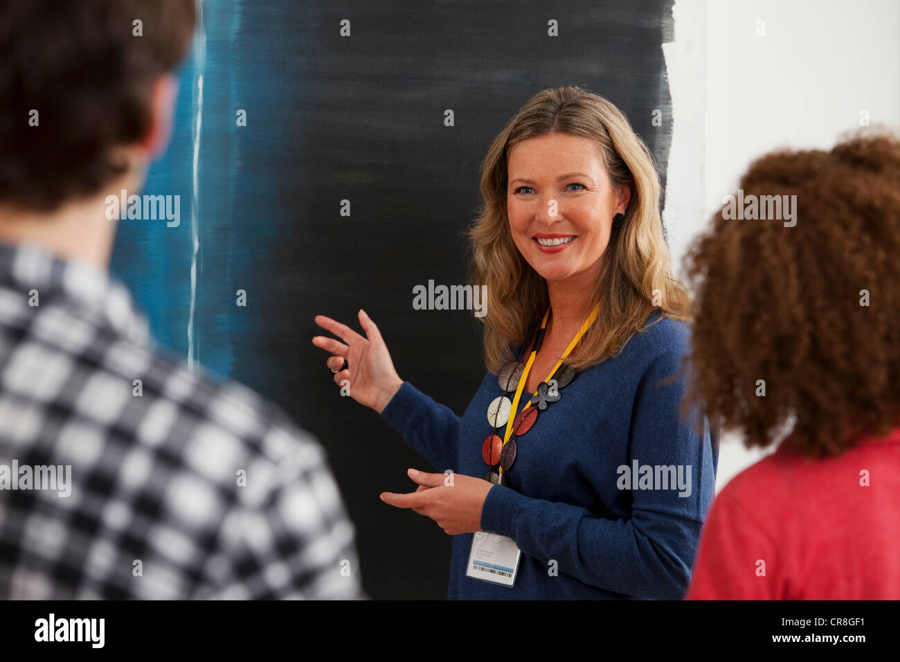 Men and women listening to guide in art gallery - Stock Image