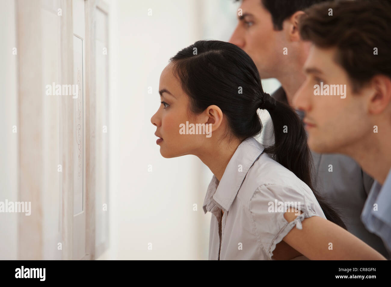 Young woman looking at picture in art gallery - Stock Image