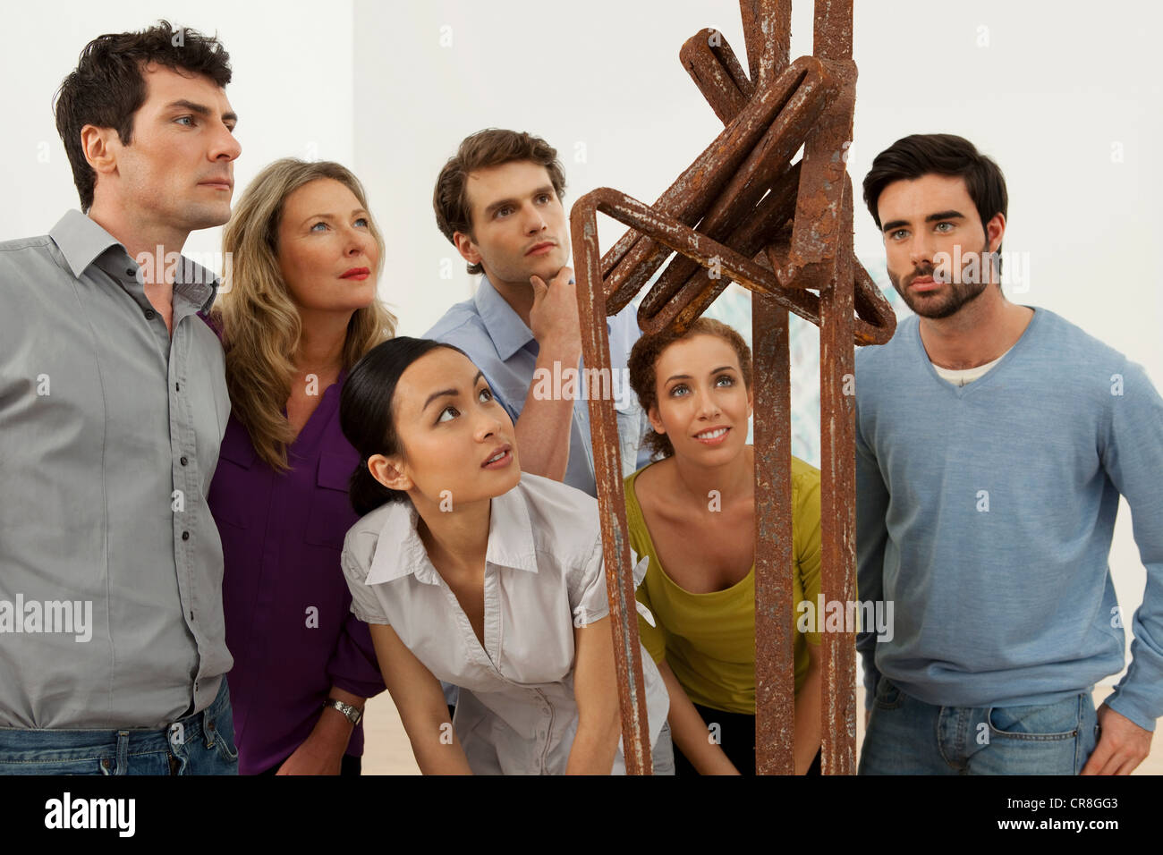 Visitors looking at sculpture in art gallery - Stock Image