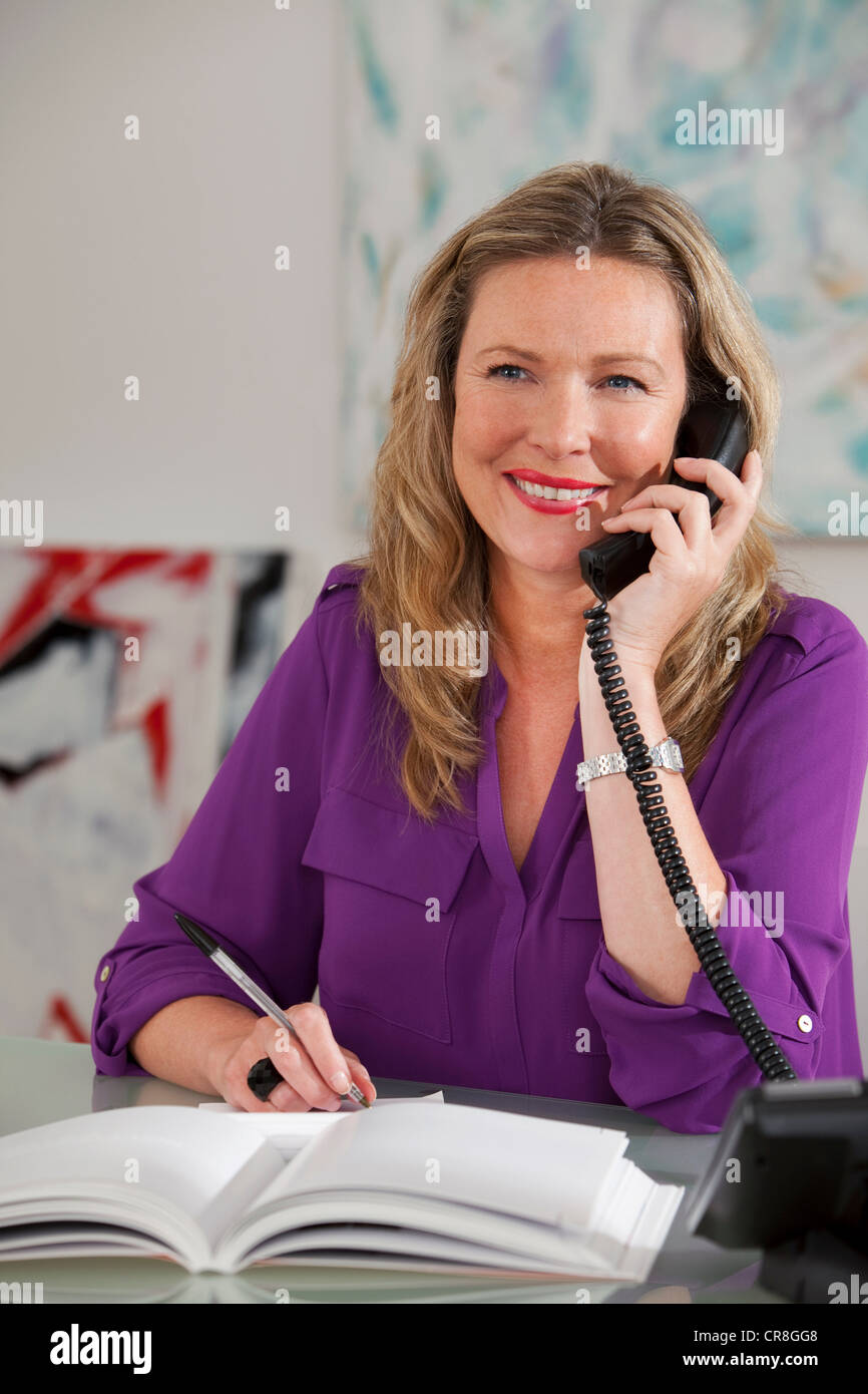 Art dealer on the phone in gallery - Stock Image