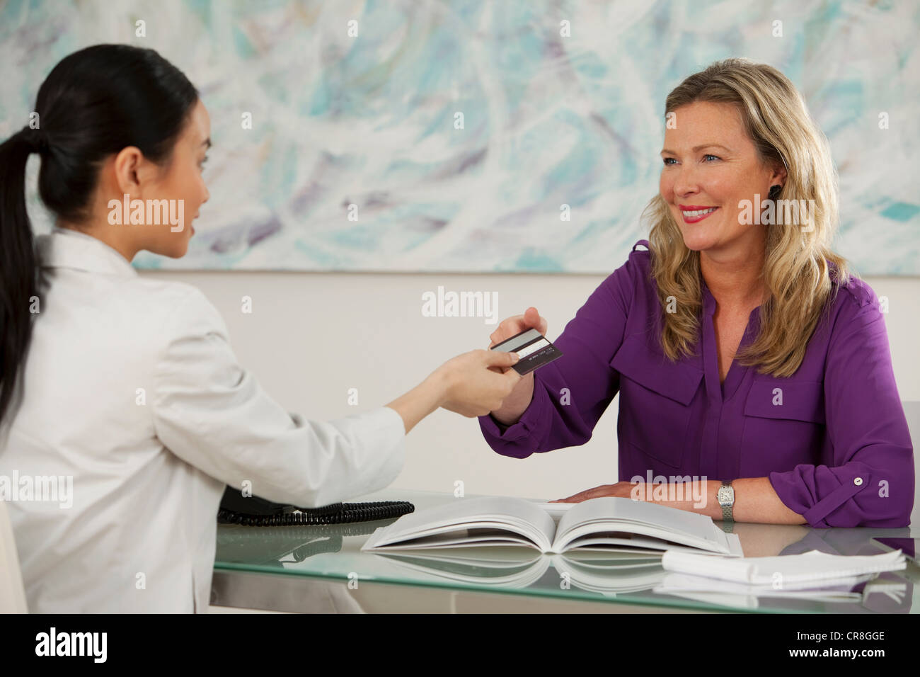 Art dealer taking credit card from young woman at desk in gallery - Stock Image