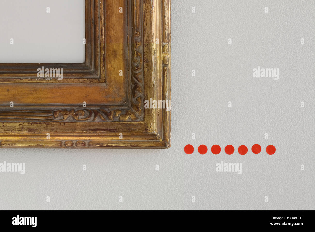 Red sold dots under picture frame - Stock Image