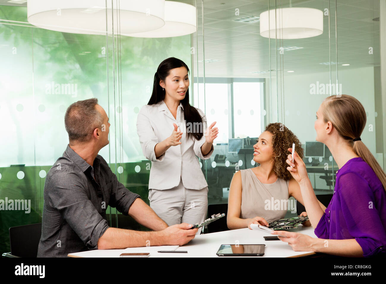 Office colleagues discussing new technologies on desk - Stock Image