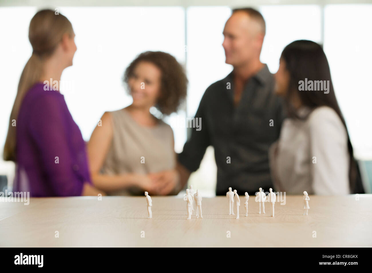 Young architect sitting at desk with model figures - Stock Image