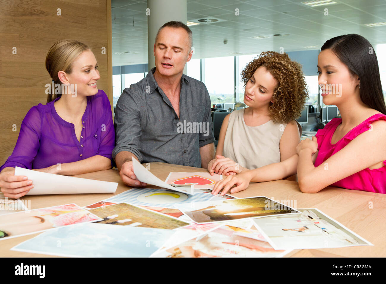Fashion designers at desk looking at imagery - Stock Image