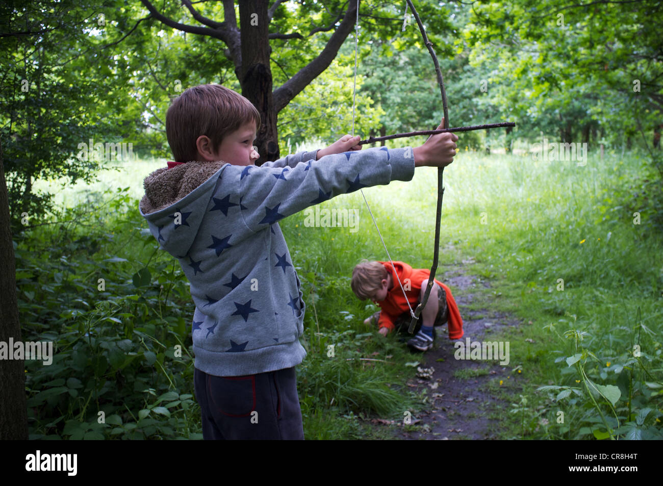 Two boys playing in woods in Sydenham, south east London including homemade bows and arrows.