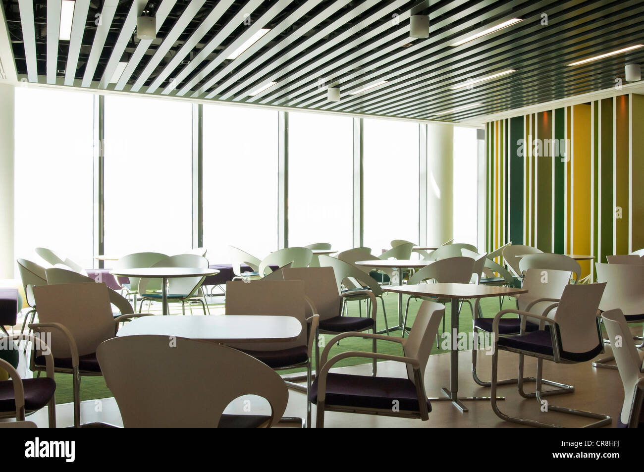 Chairs and tables in empty room of office block - Stock Image