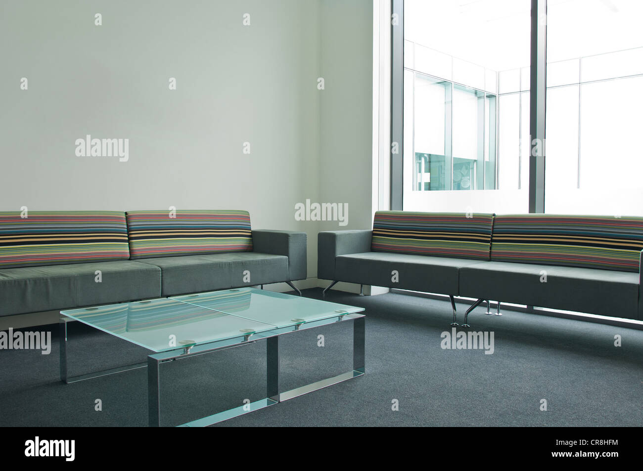 Glass table and sofas in empty office block - Stock Image