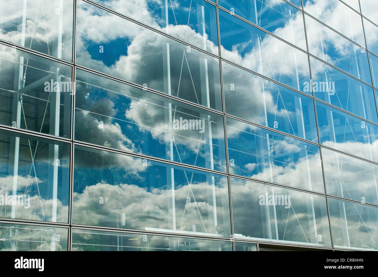Cloudy blue sky reflected in office windows - Stock Image