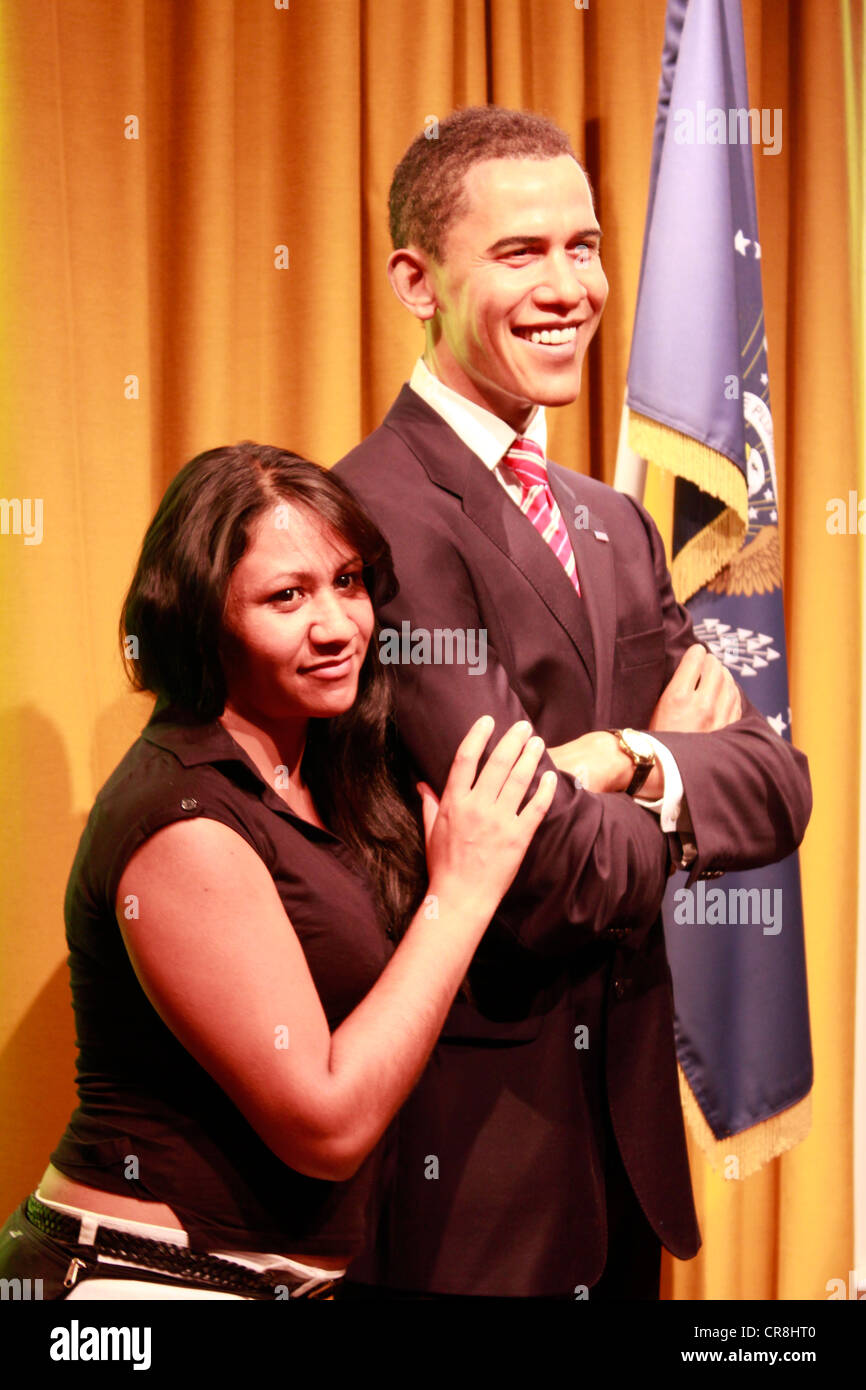 Woman posing next to the wax statue of American president Barack Obama at the madame tussauds museum - Stock Image