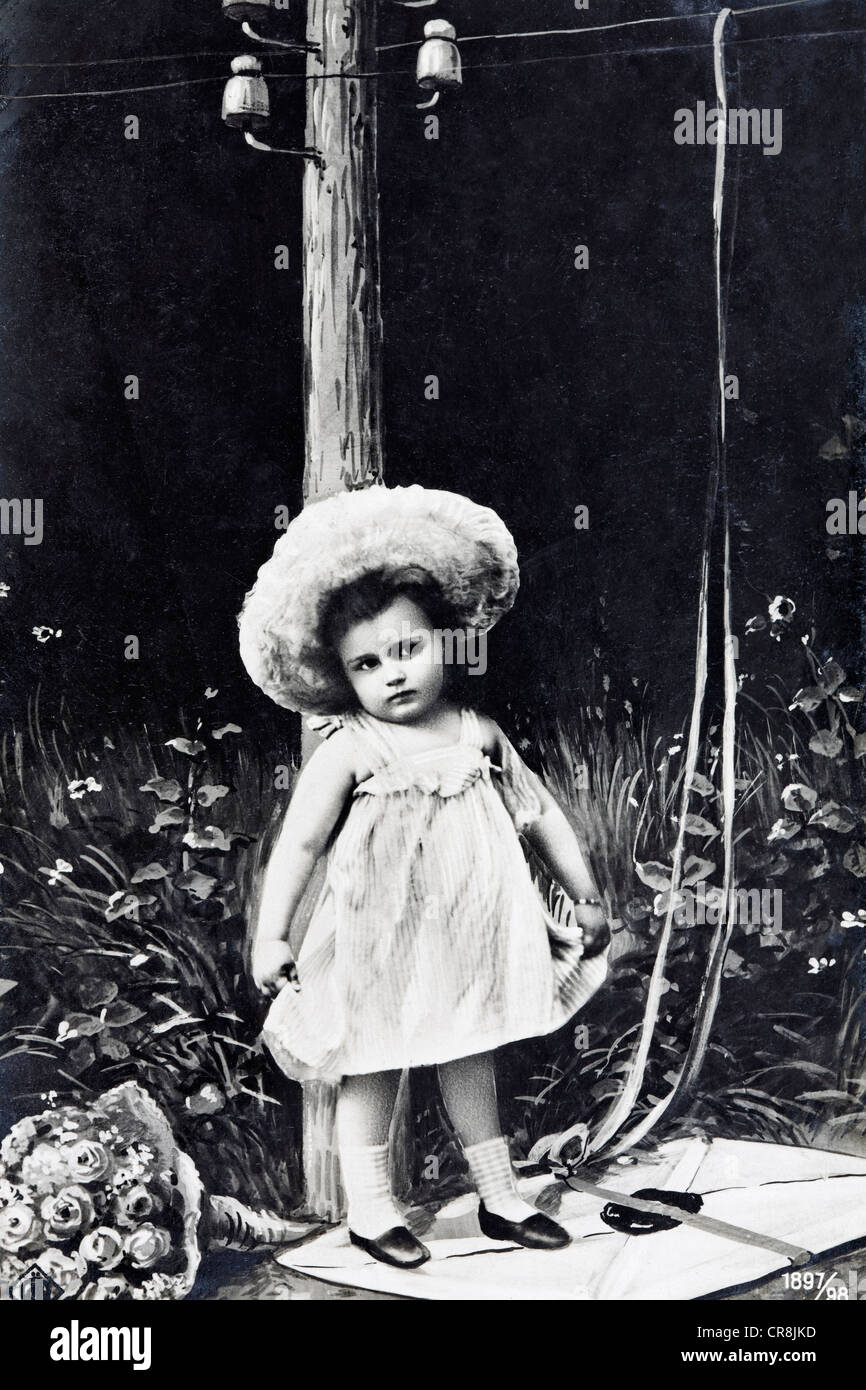 Cute little girl standing on a letter with a bunch of flowers, historical postcard, circa 1900, kitsch - Stock Image
