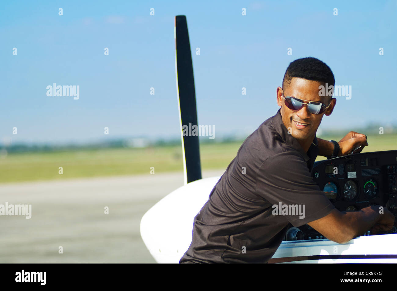 A pilot checking his plane pre-launch pauses to look over his shoulder with clenched teeth. - Stock Image