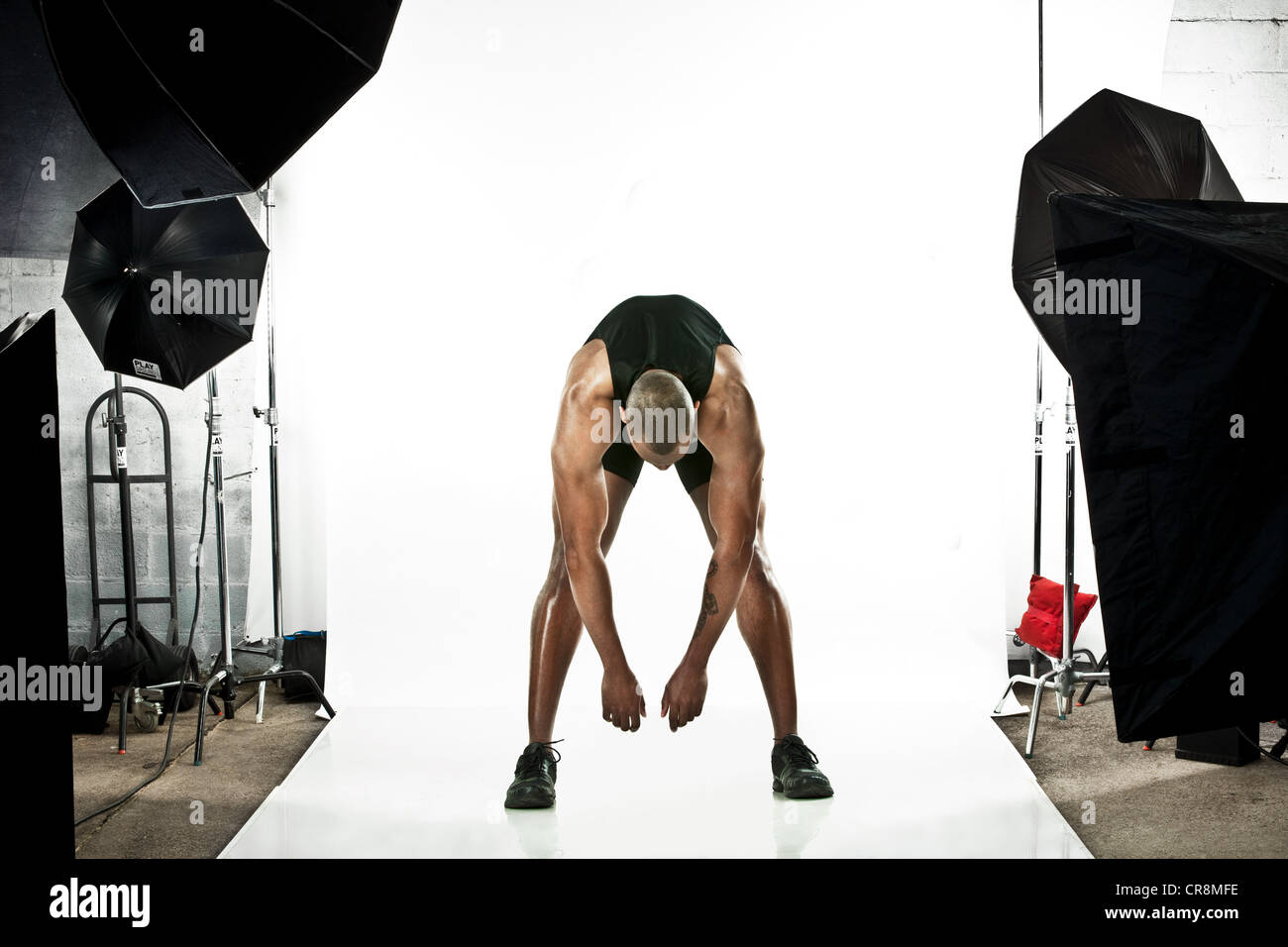 Athlete at photo shoot, stretching - Stock Image
