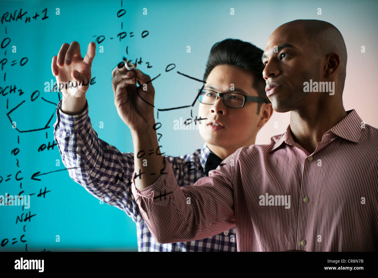 Two people writing formula on window - Stock Image