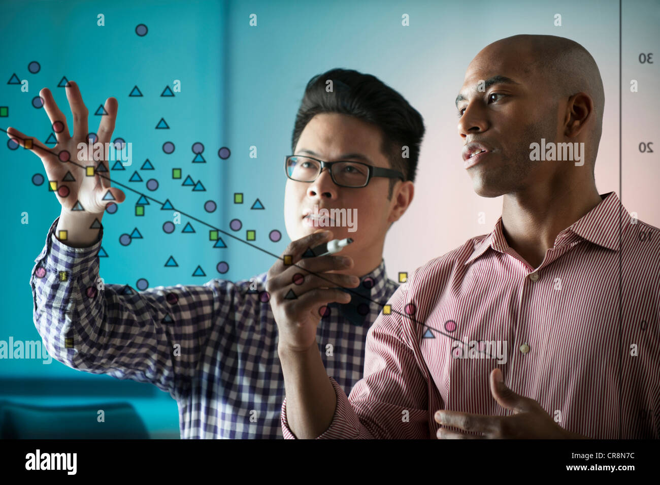 Two people looking at diagram on window - Stock Image