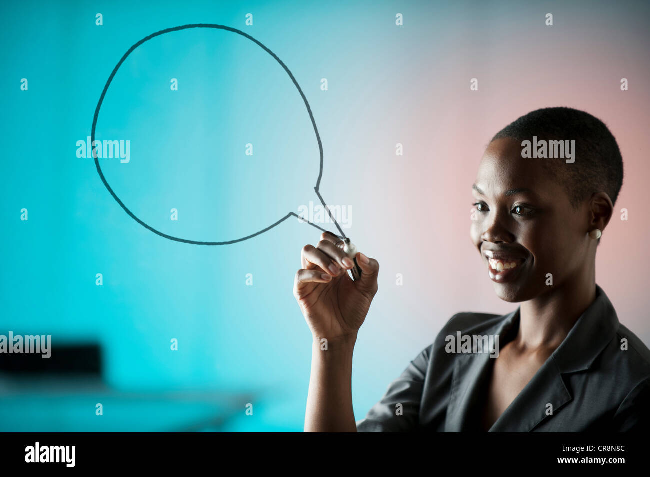Young woman drawing speech bubble on window - Stock Image