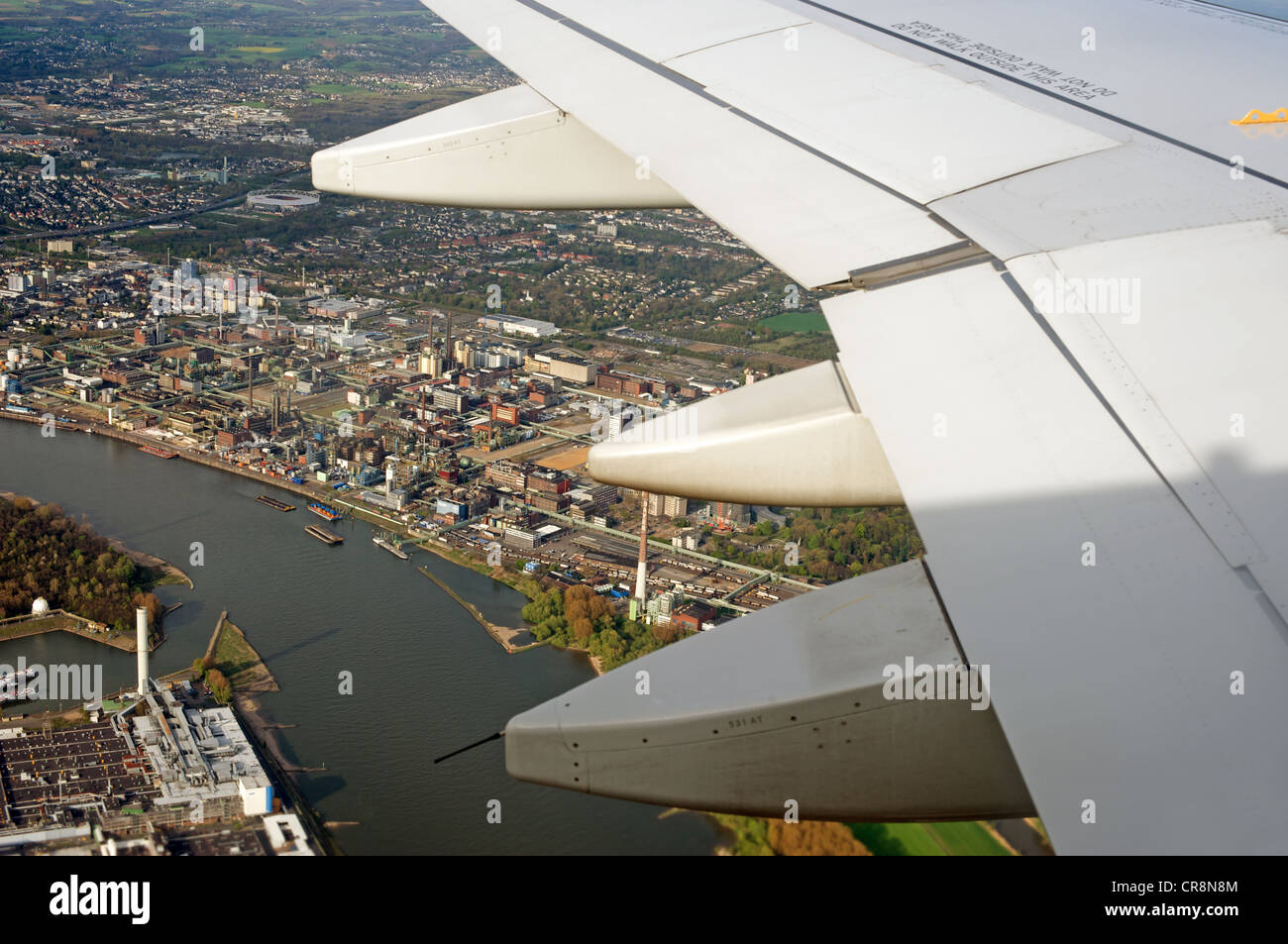 Commercial airliner flying over the river Rhine and the industrial city of Leverkusen, Rhineland, Germany - Stock Image