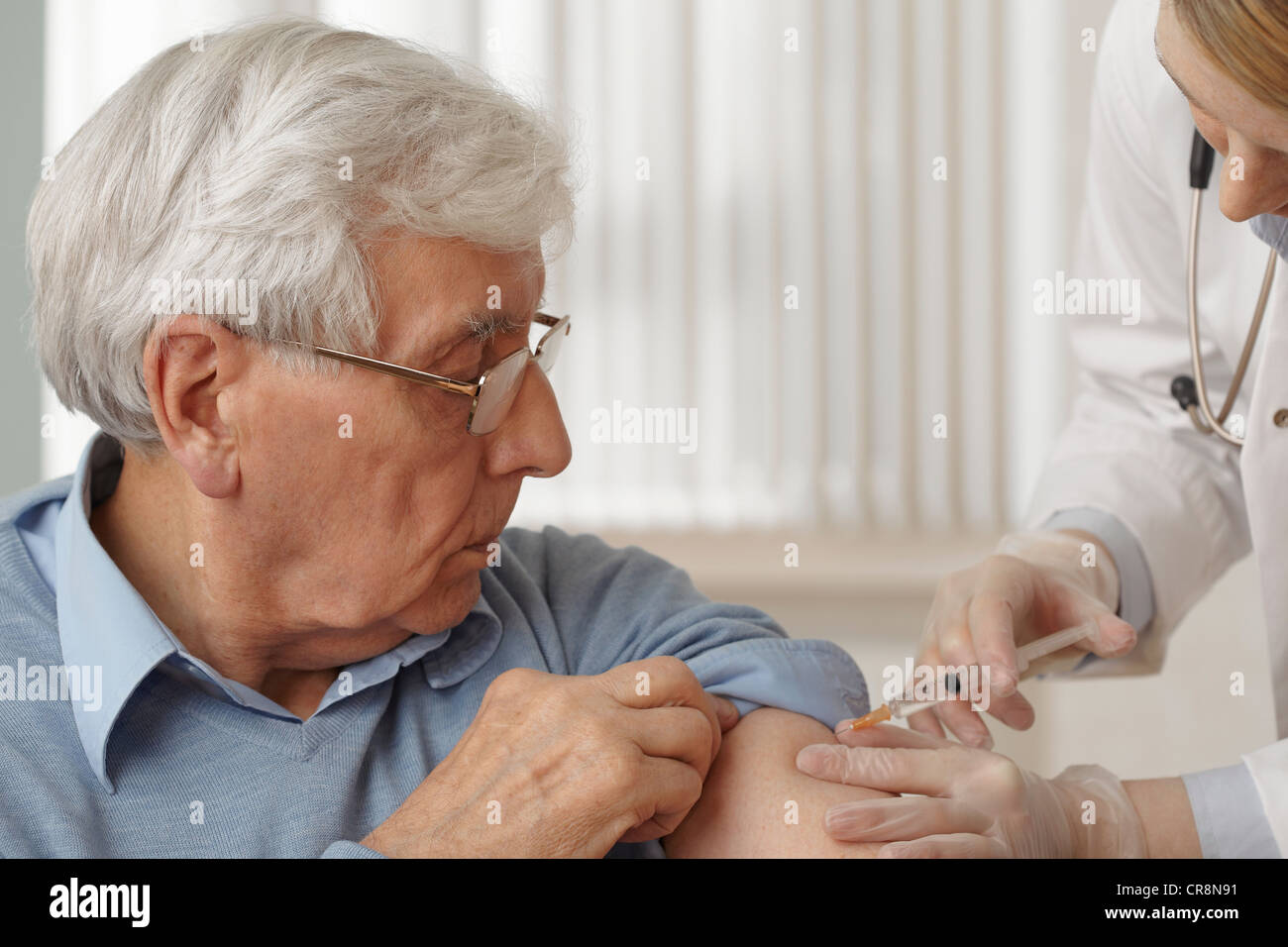 Doctor giving senior man injection - Stock Image