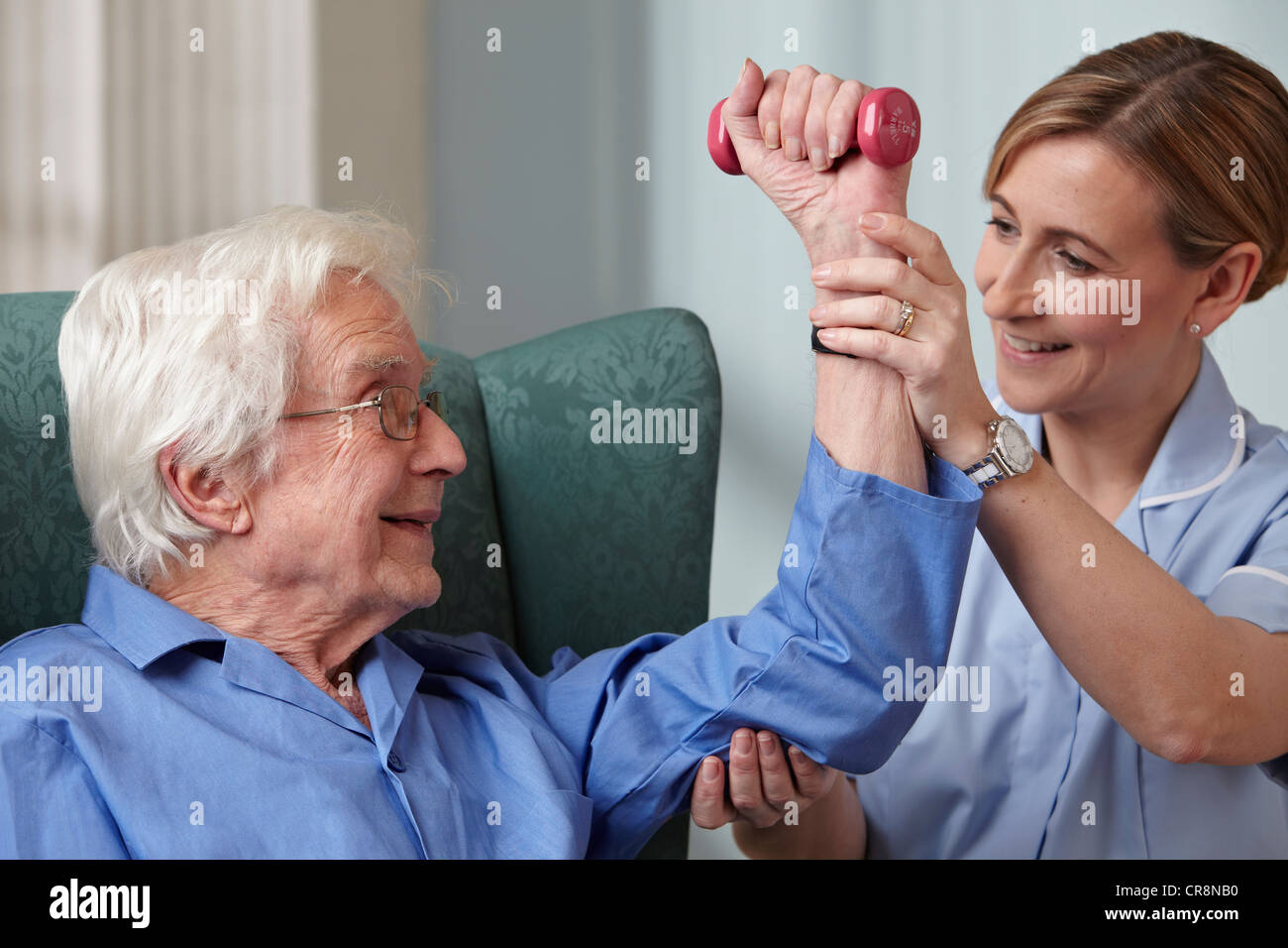 Carer assisting senior man with hand weights - Stock Image