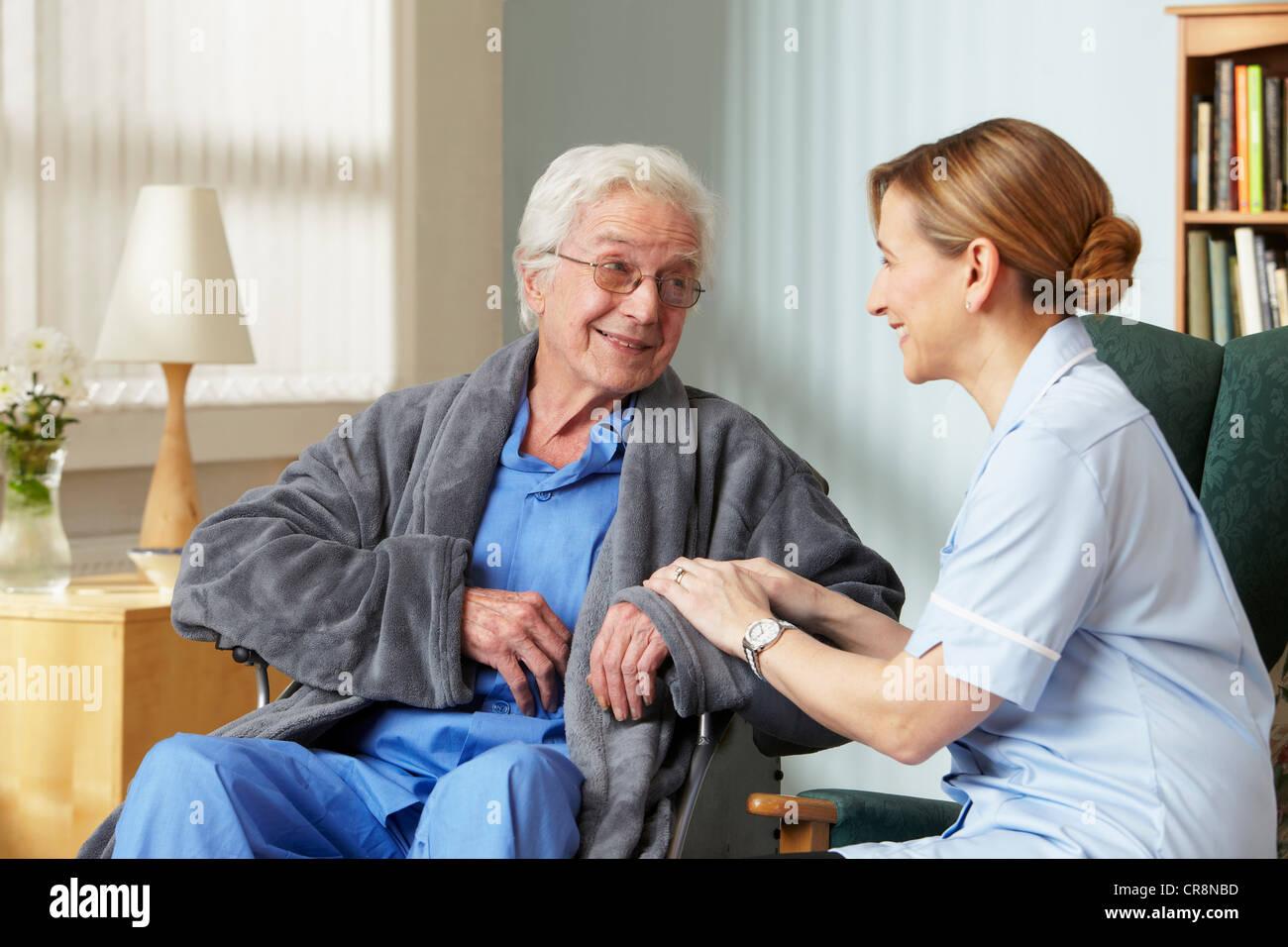 Carer touching senior mans arm - Stock Image
