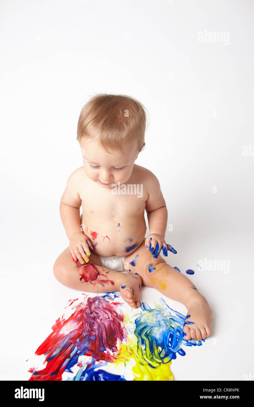 Baby looking at messy paint - Stock Image