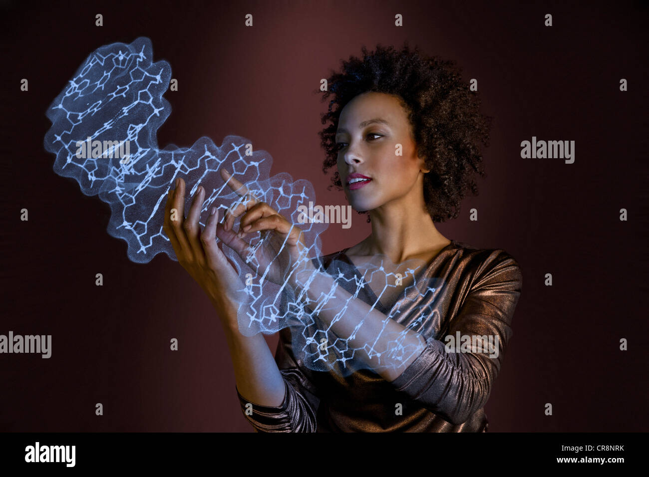 Woman interacting with holographic genome - Stock Image
