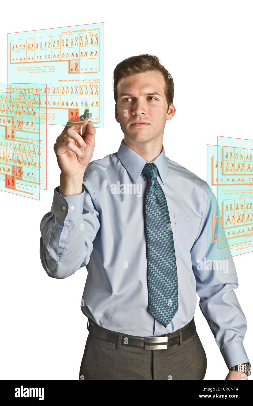 Businessman interacting with holographic screens showing chromosomes - Stock Image