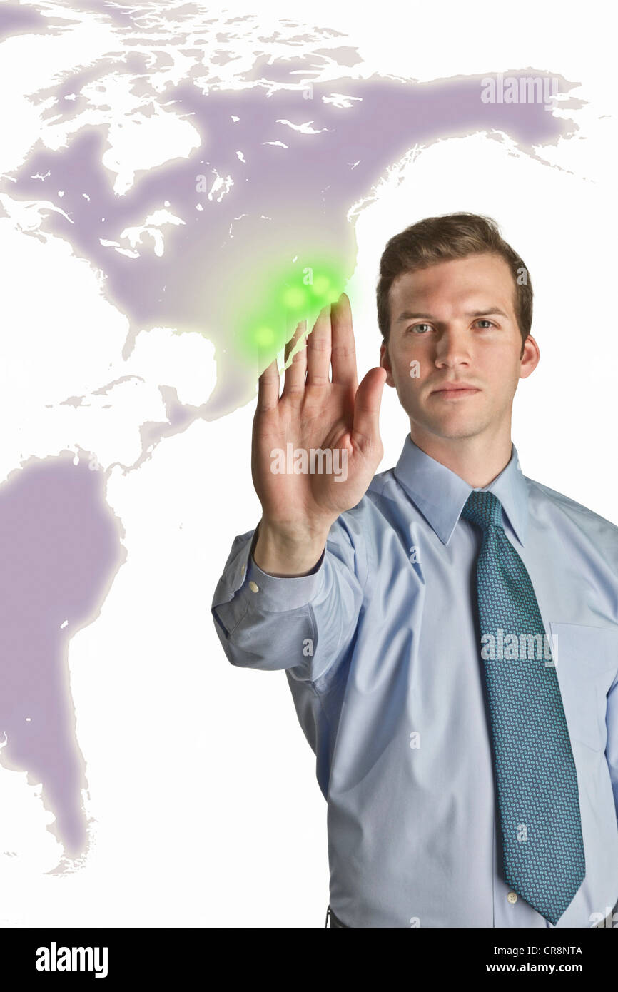 Businessman interacting with holographic map - Stock Image