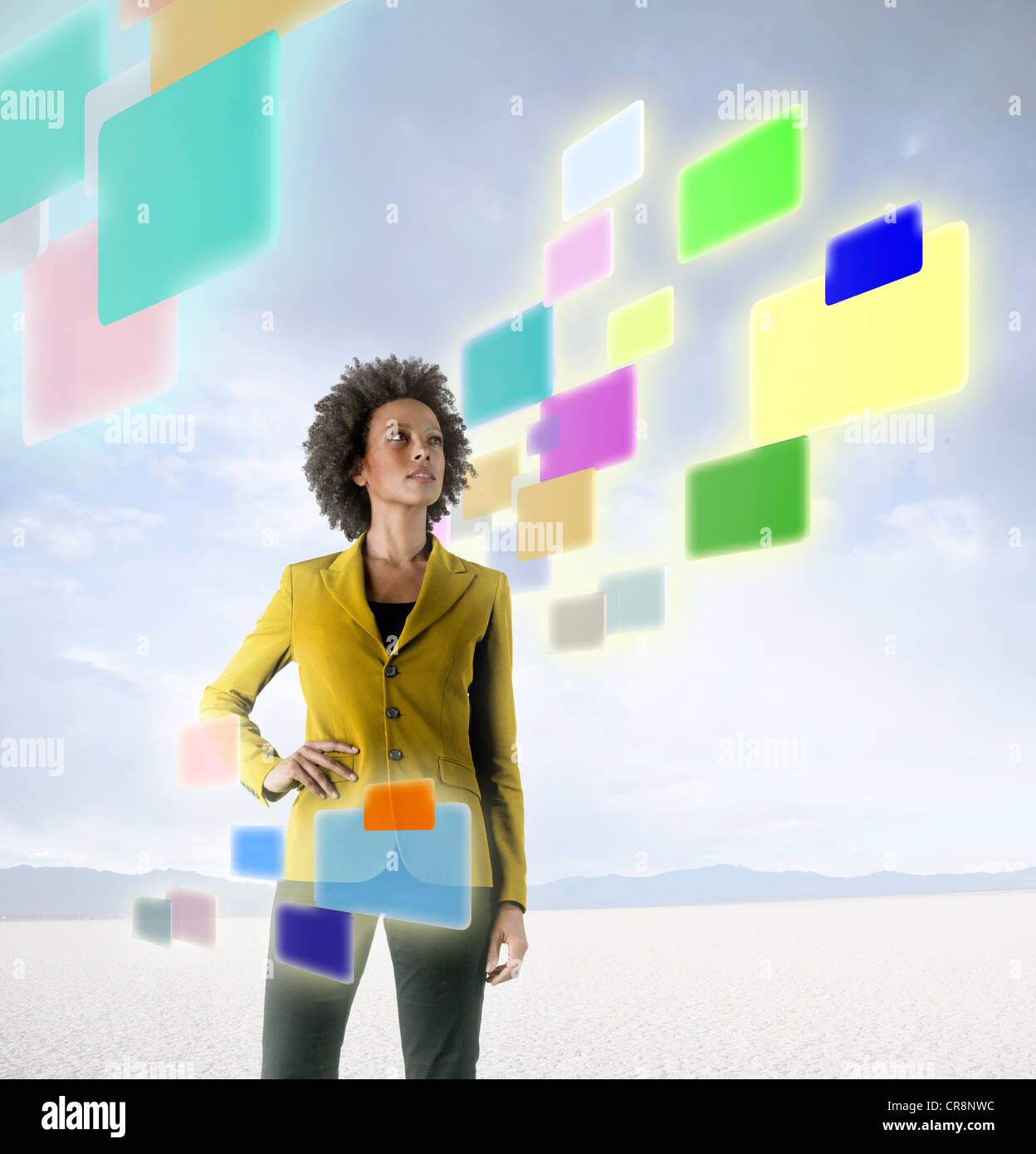 Businesswoman looking at holographic screens in desert - Stock Image