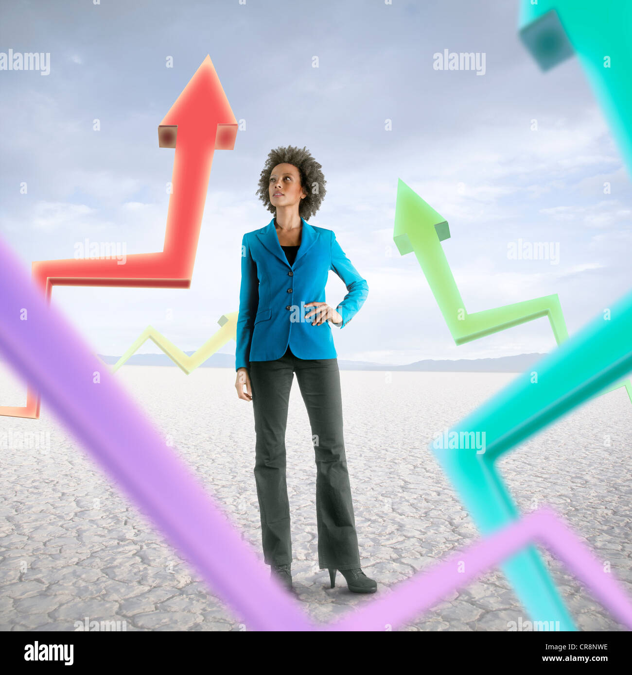 Businesswoman looking at holographic arrows in desert - Stock Image