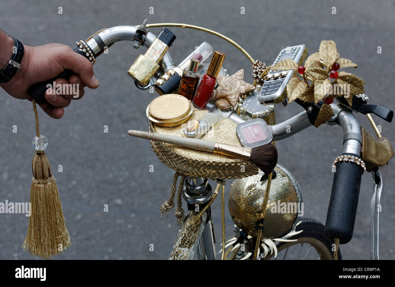 Handlebars of a ladies bicycle decorated with makeup and cell phone, Christopher Street Day in Duesseldorf - Stock Image