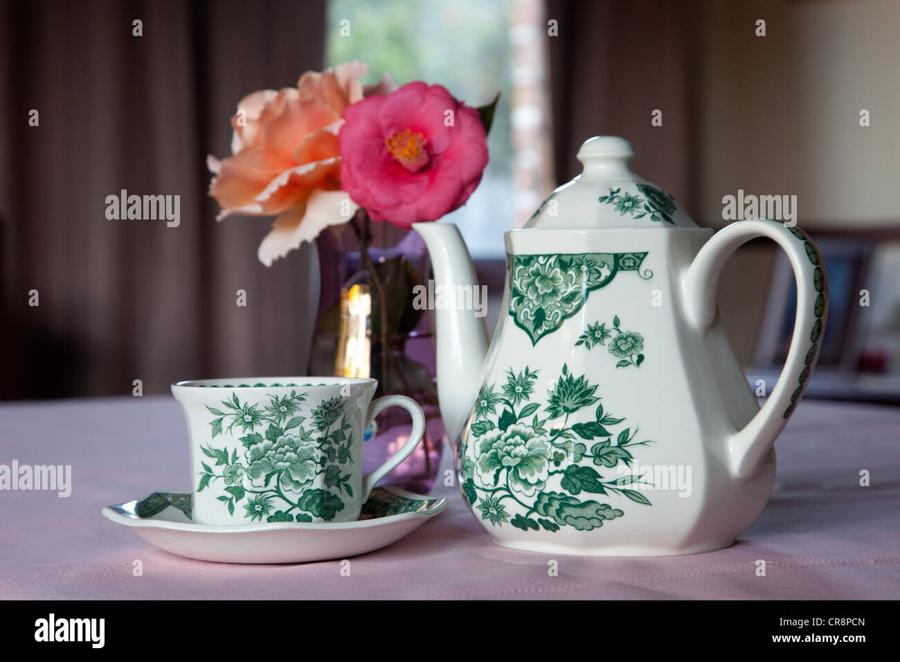 Teacup and Teapot in front of a vase of flowers in Australia Brisbane - Stock Image