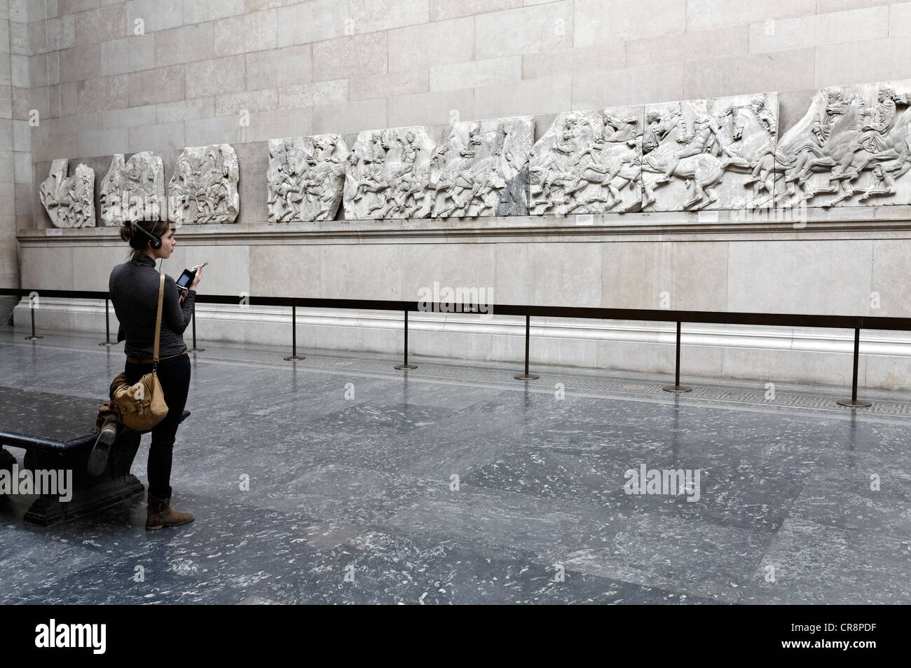Young museum visitor with audio guide looking at the Elgin Marbles, marble reliefs from the Athens Parthenon, British Stock Photo