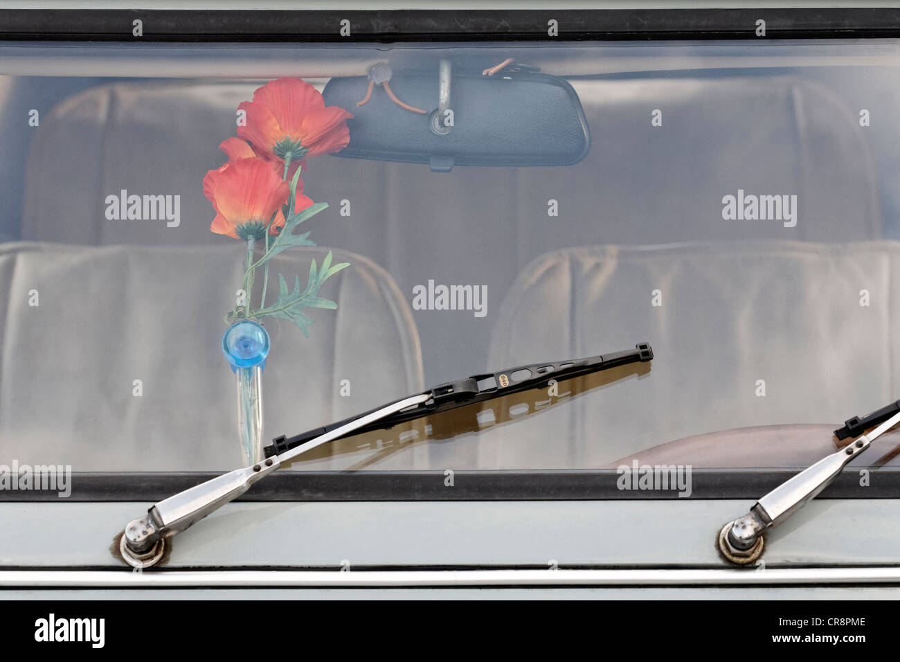 Kitschy vase of plastic flowers behind the windshield of an old Citroen 2CV, Germany, Europe - Stock Image