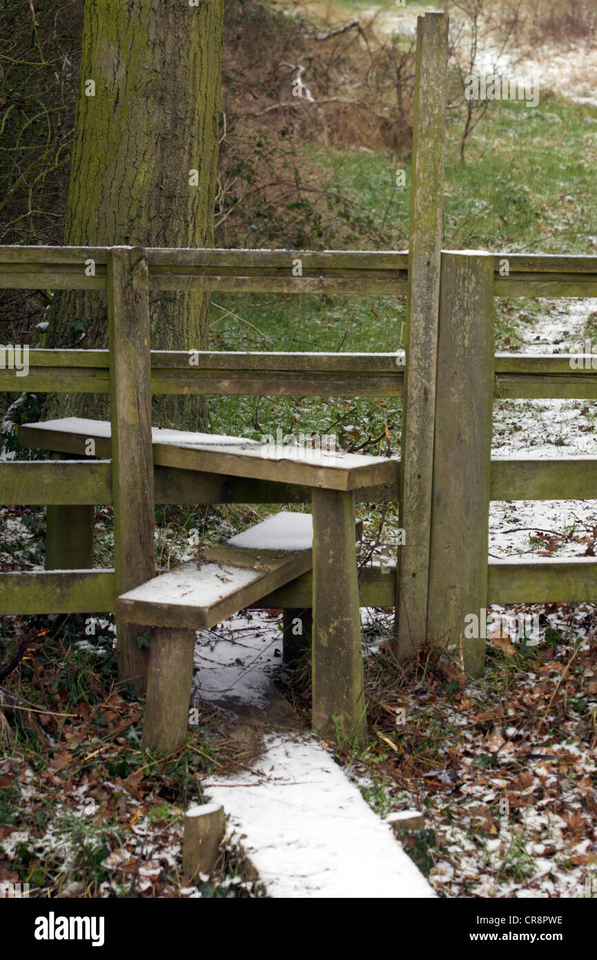 Wooden stile on footpath in the snow, Berkshire, UK. - Stock Image