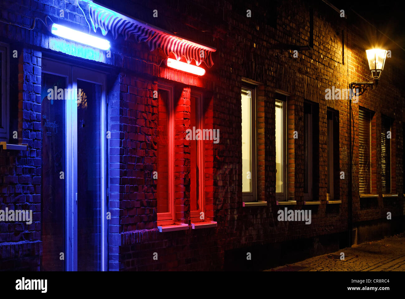Alley in the historic district, nice ambiance, blue illuminated door, red illuminated window, Duesseldorf - Stock Image