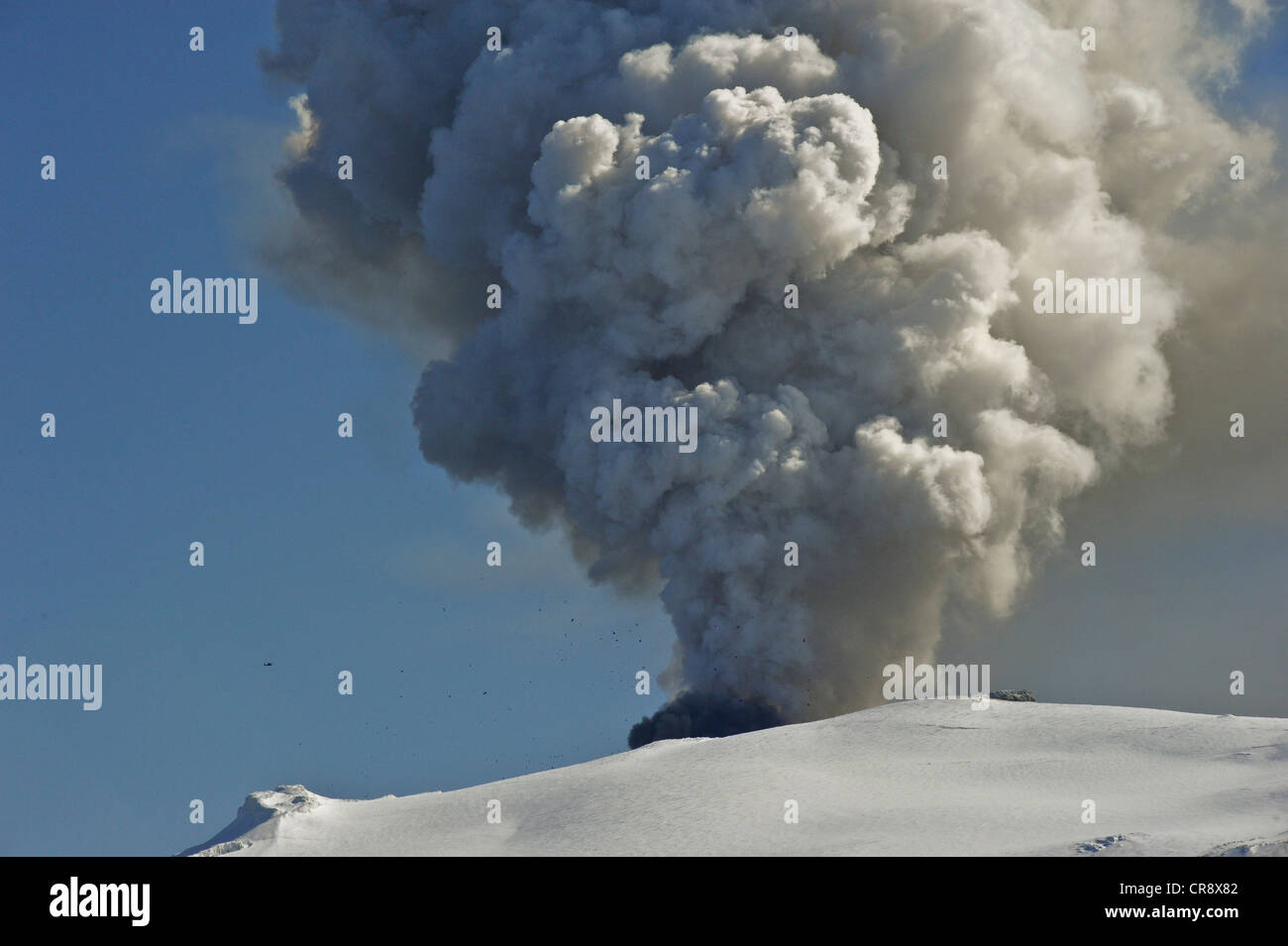 A helicopter flying in close proximity to the crater of Eyjafjallajoekull Volcano, while large lava bombs are being - Stock Image