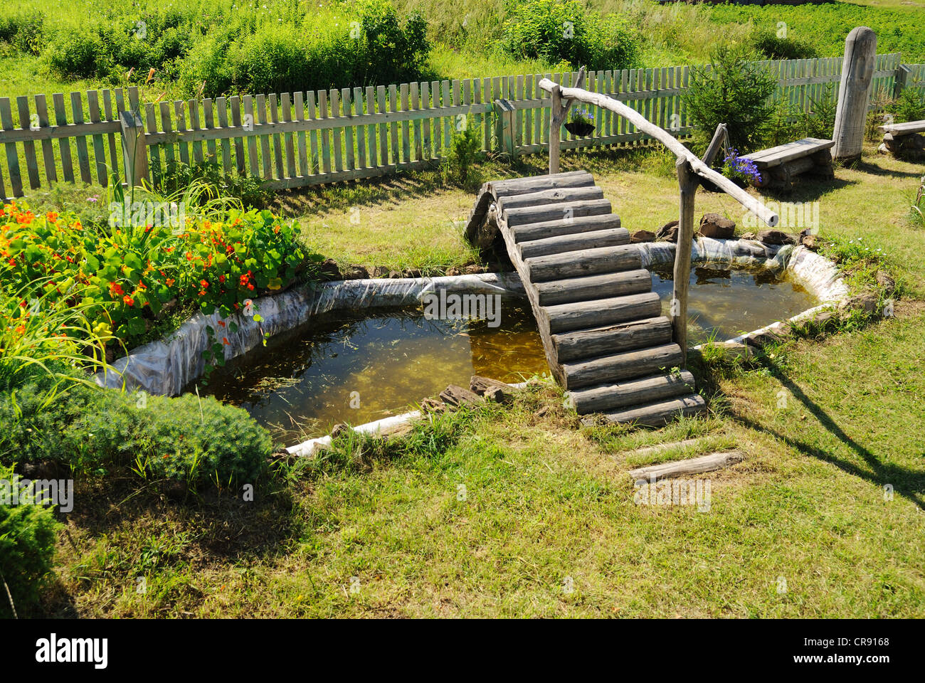 small garden pond with wooden bridge in summer - Stock Image